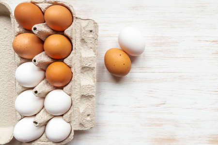Brown and white eggs in recycled cardboard box and two chicken eggs near on wood table. Free-range organic eggs in paper box. Carton container with eggs on wood background. Top view, copy space