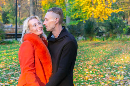 Middle-aged couple in autumn park. Smiling pair on colorful fall background. Lovely couple on autumn trees background. Couple having fun in multicolor fall park.