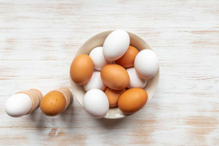 Brown and white eggs in bowl on wood background. Free-range organic eggs. Plate with brown and white chicken eggs, boiled eggs in holders on wooden table. Healthy food concept. Top view, copy space.