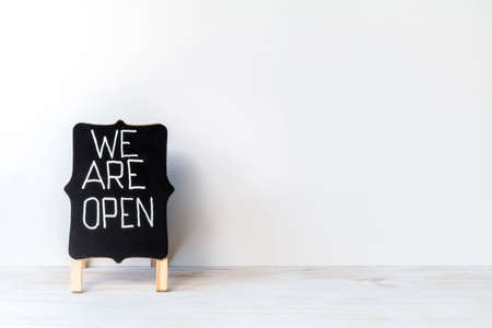 We are open - words written with white chalk on blackboard. Chalkboard with handwriting text WE ARE OPEN. Open sign. Copy space. Back to business concept 免版税图像