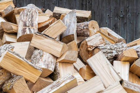Dry chopped firewood background. Preparation of firewood for winter. Rural cozy firewood backdrop. Natural, organic concept 免版税图像