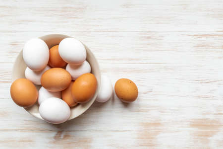 Brown and white eggs in plate and two near on wood background. Free-range organic eggs in bowl. Bowl with brown and white chicken eggs on wooden table. Top view, copy space. Natural healthy food. 免版税图像