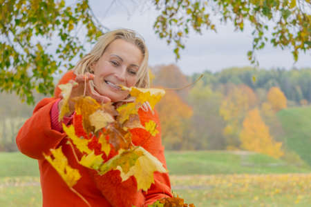 Blonde Middle-aged woman in red coat playing with autumn maple leaves in colorful fall nature background. Portrait of romantic and playful female. Smiling woman and leaves. Fall colors copy space.