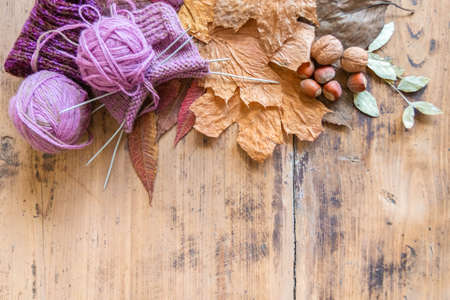 Knitted sock, ball of yarn and knitting needles on rustic table. Wool knitting, leaves and nuts on vintage wooden surface. Top view. Copy space. Cold season concept 免版税图像