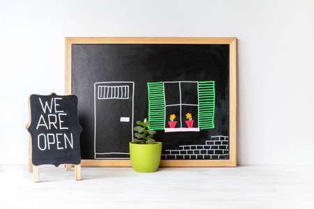 House drawing on blackboard, plant in pot and WE ARE OPEN word on chalkboard. Open singboard near house, drawn on blackboard. Open small business concept