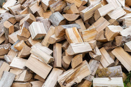 Preparation of firewood for winter. Rural cozy firewood background. Dry chopped firewood logs in pile. Natural, organic concept