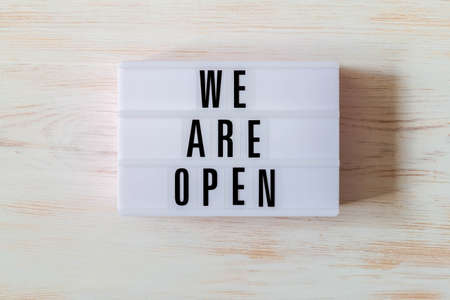 Signboard WE ARE OPEN of lightbox on wood background. Open sign hanging on vintage wooden wall. Opening sign of cafe, bar, or restaurant. Business open and welcome. Concept of quarantine mitigation