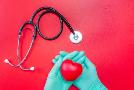 Medical stethoscope and hands in rubber gloves holding red heart on red background. Flat lay of heart in hands and stethoscope. Mockup for medical and health care. Healthcare and cardiology concept. Copy space.