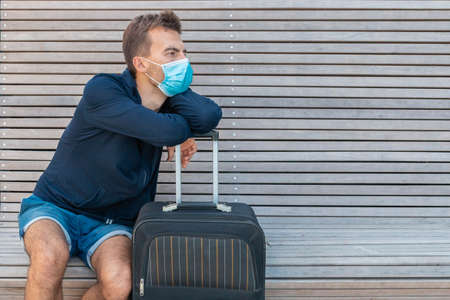 Man wearing protective mask holding suitcase and sitting on bench. Traveler in face mask with his luggage in airport terminal. Life during coronavirus. COVID-19 outbreak prevention.