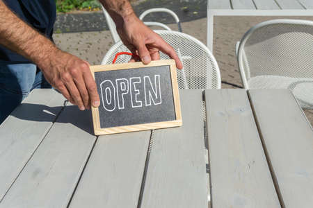Handwritten Open sign in hands of waiter on cafe table outside. Hands holding signboard Open in open-air snack bar. Blackboard with inscription as symbol of reopened small business