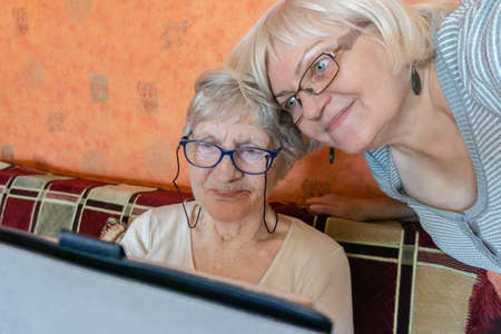 Old mother and daughter reading good news online inside. Woman teaching senior mother to use internet at home. Senior woman with her daughter looking at modern gadget indoors.
