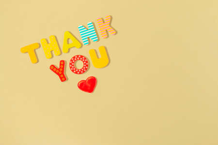 Red heart and words THANK YOU of colorful wooden letters on yellow background. Thank you inscription and heart. Appreciation, gratitude and love concept.