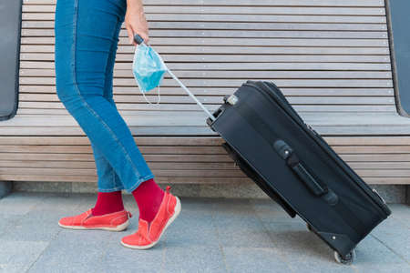 Cropped view of woman, holding suitcase and protective face mask. Traveler holding medical mask in hand and moving luggage. Legs of woman, mask and baggage. Travel during coronavirus concept