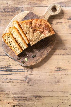 Freshly baked pumpkin bread loaf on cutting board on rustic table. Homemade bread with pumpkin seeds. Vertical orientation