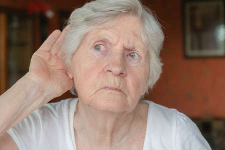 Senior woman holding hand to ear. Old lady having hearing problems. Portrait of grandmother trying to hear something. Problems of hearing, seniors hearing loss concept.