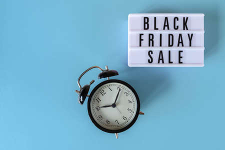 Black Friday sale text on white lightbox and alarm clock on blue background. Thanksgiving promotion advertising. Black Friday sign with copy space. 免版税图像