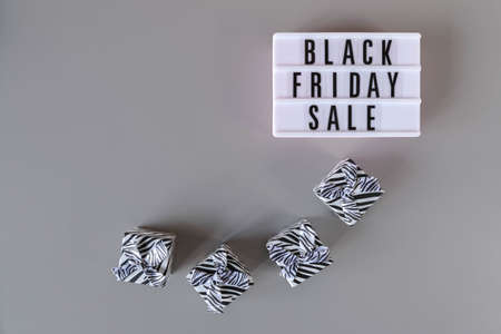 Black Friday sale text on white lightbox and gift boxes on gray background. Black Friday sign with copy space. Thanksgiving promotion advertising 免版税图像