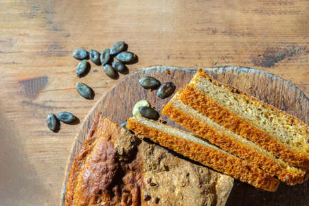Top view of homemade baked pumpkin bread and seeds on cutting board. Fresh pumpkin bread on rustic wooden table closeup. Home bread-making concept