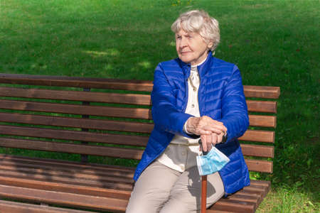 Old woman with protective face mask on cane sits on bench in park. Senior woman sitting on bench outdoors and holding walking stick with medical mask. Gray-haired lady sitting in park and enjoying sun