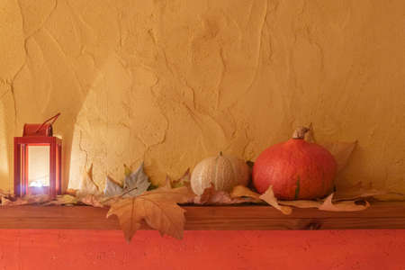 Orange pumpkin, burning candle in lantern, dry fall leaves on wood board and yellow wall background. Halloween vintage background. Mockup for Halloween 免版税图像