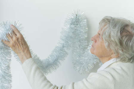 Old woman hanging silver garland for Christmas on white wall with copy space. Gray hair senior woman holding Christmas decoration on white background.