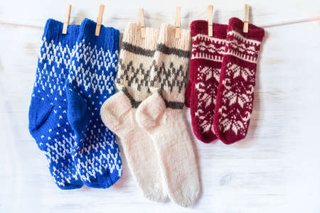 Knitted wool socks and mittens hanging on clothespins on wooden background. France flag colors vintage decoration. Winter and Christmas concept Foto de archivo