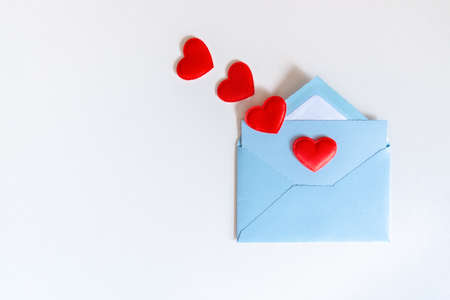 Flying red hearts from love letter in blue envelope on white background. Love letter with hearts and copy space. Gratitude to doctors and nurses. Valentines, Mother, Women's day greetings