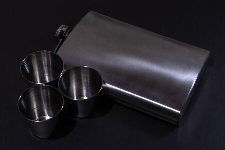 Metall hip flask on black backdrop. Flasks for alcohol