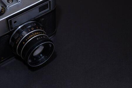 Old film camera. Black background close-up. Vintage photo