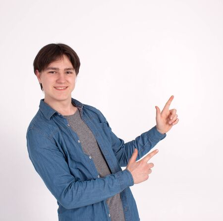 young man nerd pointing finger aside at blank copy space, isolated on white grey studio background.