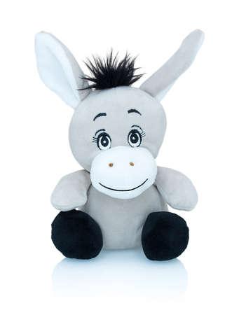 Peluche burro sonriente gris aislado sobre fondo blanco con reflejo de sombra. Juguete salvaje africano aislado sobre fondo blanco. Marioneta de peluche Jackass sobre fondo blanco. Foto de archivo