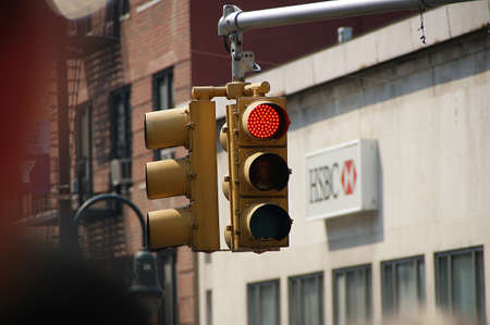 Manhattan, New York City, New York - June 10 2009. Red color traffic light with HSBC Bank building in the background.