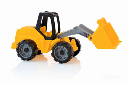 Yellow excavator isolated on white background with shadow reflection. Plastic child toy on white backdrop. Construction vehicle. Children's toy. Tractor Toy. 版權商用圖片