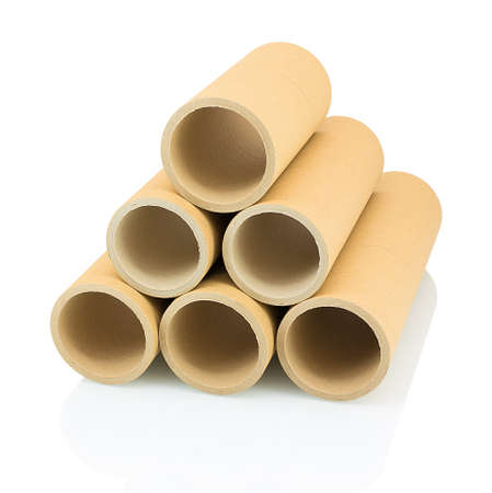 A bunch of brown industrial paper core isolated on white background with shadow reflection. A lot of paper cores or paper tubes on white backdrop. Brown paper rolls.