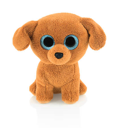 Cute dog doll with blue eyes isolated on white background with shadow reflection. Playful bright brown dog toy sitting on white underlay.