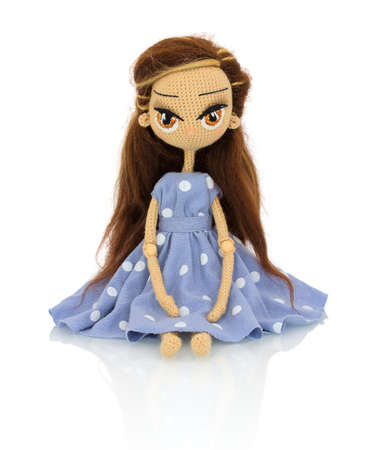 Cute handmade crochet doll with speckled blue dress isolated on white background with shadow reflection. Playful crochet brown hair doll sitting on white underlay. Knitted doll.