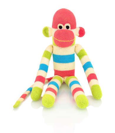 Cute handmade crochet monkey doll isolated on white background with shadow reflection. Playful crochet green pink blue white monkey sitting on white underlay. Knitted ape.