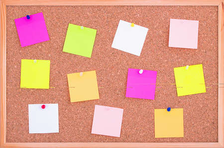 Cork board wood background with post it notes in different radiant colours. Cork board surface. Close up background of cork board wood surface with colorful notes. Cork table. 版權商用圖片