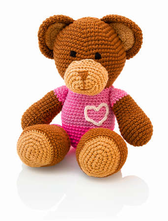 Cute handmade crochet bear doll isolated on white background with shadow reflection. Playful crochet brown pinky bear sitting on white underlay. Knitted bear.
