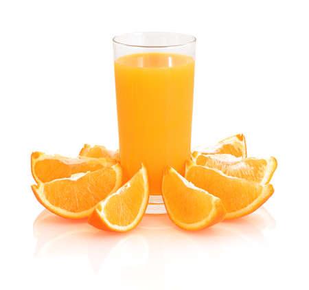 Glass of orange juice with fresh shiny orange slices around the glass isolated on white background with shadow reflection.