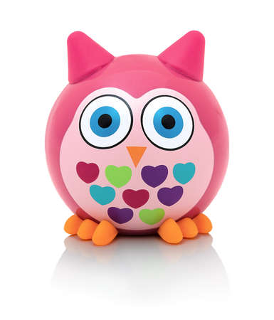 Owl toy isolated on white background with shadow reflection. Owl the bird of prey on white backdrop. Rainbow colored plastic toy. Pink cute owl.