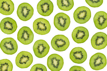 Green slices of kiwi fruit isolated on white background, overhead shot. Sliced kiwi photographic pattern, top view. Layout of sliced kiwi pieces on white backdrop. Kiwi seamless pattern.