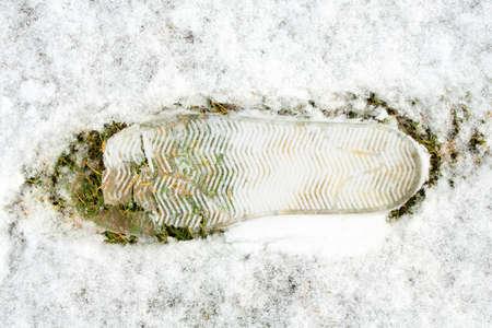 Close up of footprint on snow on green grass. 版權商用圖片
