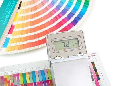 Printed color swatch with density meter and paint guide isolated on white background. Color density check in printing process. Measuring color density with densitometer. Density meter and ink sampler.