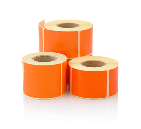 Orange label roll isolated on white background with shadow reflection. Color reel of labels for printers. Labels for direct thermal or thermal transfer printing. Orange stickers. 版權商用圖片