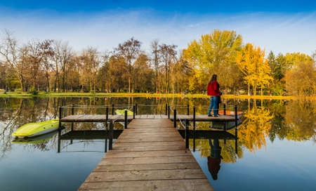 amazing autumn colors in the city park surrounded with trees lake and wooden deck Stock Photo