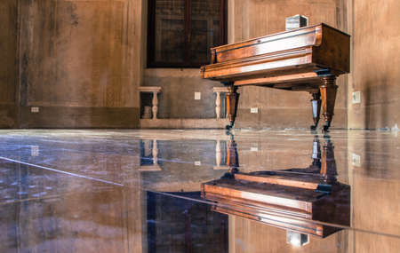 Old rustic piano on stands with wheels in empty room with polished glass look floor making reflection of piano and whole room symmetrical
