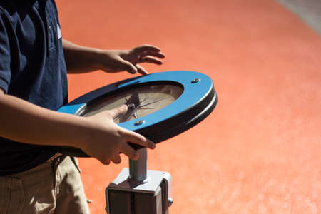 Young boy rotates play wheel which is actually a compass and through playing kid is learning how to use compass at the public playground in Abu Dhabi