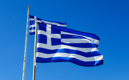 Flag of Greece Flying in Wind and Blue Sky