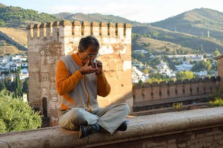 paz interior: Paz interna, la tranquilidad y la presencia se ilustra por un hombre que disfruta del medio ambiente en el histórico palacio de la Alhambra en Granada, con una taza de té en sus manos.
